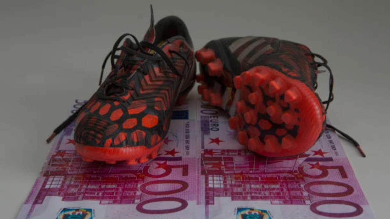 Un paio di scarpe appoggiate su due banconote da 500 euro
